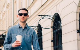 Man walks around the street with white cup of coffee Stock Images