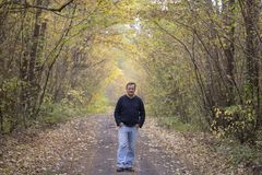 Man walks in the autumn forest along the road. People and lifestyle concept stock images