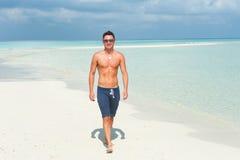 Man walks on the beach with the blue sea Royalty Free Stock Photos