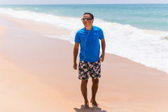 Man walks on the beach with the blue sea and the beautiful sky with white clouds. Summer time Stock Photography