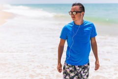 Man walks on the beach with the blue sea and the beautiful sky with white clouds. Summer time Stock Photos