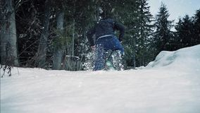 Man Walks Through Deep Snow In The Woods. Man walks through thick snow near forest in snowfall stock footage