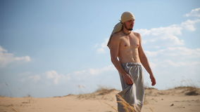 A man walks through the desert. Man walking on hot sand under the scorching sun in the desert stock video footage