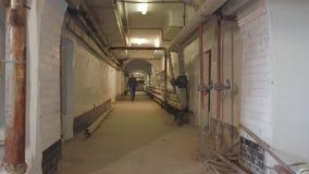 A man walks down a long basement corridor