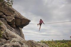 A man walks down slackline. A young man balances on a highly tense slackline stock photos
