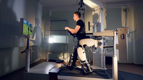 A guy tracks a TV avatar during his exoskeleton training.