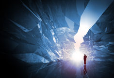 Man walks through the fantasy crystal corridor. With rugged walls and bright glowing end Stock Image