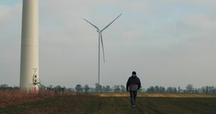 A man Walks In A Field On Background Rotating Windmill. The Power Of The Wind. A Clean And Renewable Energy Solution. Wind Turbine
