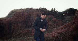 Man walks into frame and stands, looking out over vast ocean and cloudy sky in Ireland, model released. 4k stock video footage