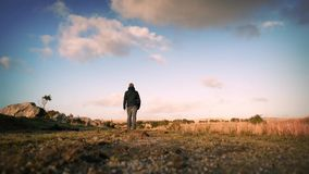 Man Walks On Hilltop. Man walking along rugged path on sunny hilltop stock footage