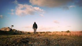 Man Walks On Hilltop. Man walking along rugged path on sunny hilltop stock video footage