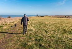 Reculver, Kent, UK along the cliff top walk on the coast near to. A man walks his dog heading to Reculver Towers,  Reculver, Kent, UK along the cliff top walk on Stock Photography