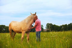 A man walks with his horse Royalty Free Stock Photo