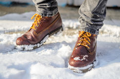 Man Walks In The Snow. Feet Shod In Brown Winter Boots. Stock Photos