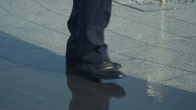 Man walks near the fountain, wet shoes, close-up. Close-up. Slowmotion. Man wearing suit and black shoes walks over the tile. Man slowly steps over the water stock footage