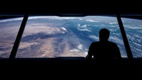 Astronaut Looks Out At Earth From Orbit. Man walks over and looks at the earth from a slowly rotating space station