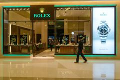 Man walks past Rolex Authorized Dealer. March 9, 2018. A man walks past an official Rolex Boutique store, with an advertisement of the Rolex Sea-Dweller on stock photos