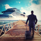 Man walks on a pier carrying a suitcase. Man boarding on a cruise ship carrying his trolley Stock Photography