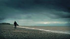 Man Walks On Rocky Beach stock footage
