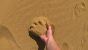 A man walks on the sand in the desert. He takes a handful of sand with his hand, passes sand through his fingers. Sand