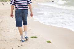 Man walks on the sea beach Stock Image