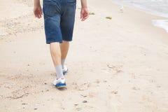 Man walks on the sea beach Stock Photos