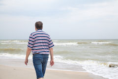 Man walks on the sea beach Royalty Free Stock Image