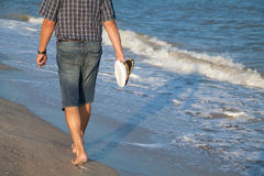 Man walks on the sea beach Stock Images
