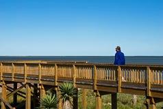 A man walks on seaside boardwalk stock photo