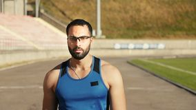 Man Walks in Stadium. Serious good-looking man walking around the stadium, doing outdoor exercise to improve health state and physical condition stock video