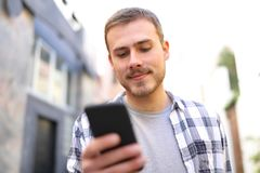 Man walks in the street using a smart phone royalty free stock photography