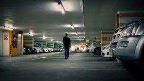 Man Walks To Car In Parking Garage stock video footage