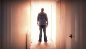 Man walks through door into bright light