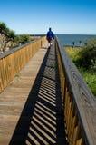 Man walks toward ocean on boardwalk stock image