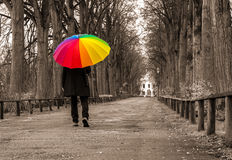 Man walks under rainbow umbrella Stock Photo