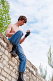 Man on the wall. A man sitting on the wall and looks at his hand Royalty Free Stock Photography