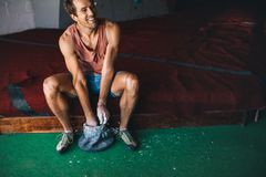 Man wall climber coating hands with gripping powder. Smiling man at a wall climbing gym applying magnesium chalk powder on hands from a bag Royalty Free Stock Photo