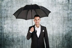 Man by the wall with umbrella. In his hand over retro background Royalty Free Stock Photos
