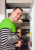 Man wanting to feed little kitten. Man at open refrigerator with kitten in arms stock images