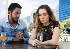 Man wants forgiveness from sad woman. Man wants forgiveness from sad women in restaurant outdoor in the city in the summer royalty free stock photos
