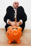 Man wants to break piggy bank. Man holding hammer over orange piggy bank Stock Photo