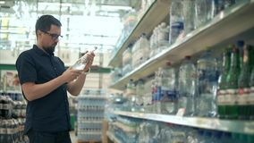 Man buys mineral water in supermarket. Man wants to buy cold bottle of mineral water in supermarket. Reading lable, shaking bottle, glass bottle. Wants to drink stock footage