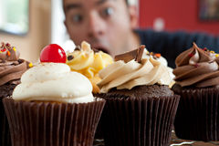 Man Wants to Eat Cupcakes. Close up of some decadent gourmet cupcakes frosted with a variety of frosting flavors. Shallow depth of field with the face of a royalty free stock image