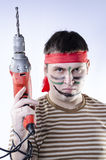 A man in war paint with a drill Stock Image