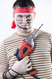 A man in war paint with a drill Royalty Free Stock Photo