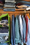 Private house closet with well organized casual man clothes. Man wardrobe with variety of shirts hung on hangers and pile of jumper, jeans and pants lain on a royalty free stock images