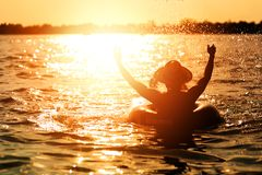 A man ware hat and he is on swim tube in the water. He is hands up to make water splash. A man ware hat and he is on swim tube in the water. He is hands up to stock images