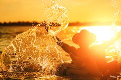 A man ware hat and he is on swim tube in the water. He is hands up to make water splash. stock photos