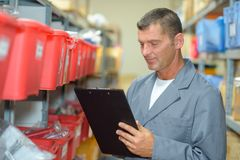 Man in warehouse with clipboard. Man Stock Photography