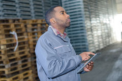 Man in warehouse in front stacks pallets. Man in warehouse in front of stacks of pallets Royalty Free Stock Photography